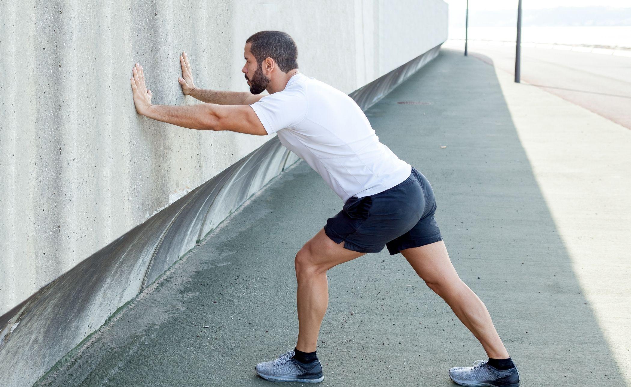 man stretching calf at a wall